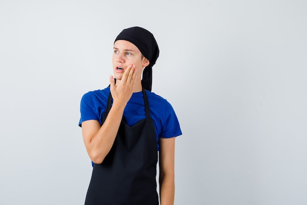 Young teen cook with hand on cheek, looking away in t-shirt, apron and looking focused. front view.