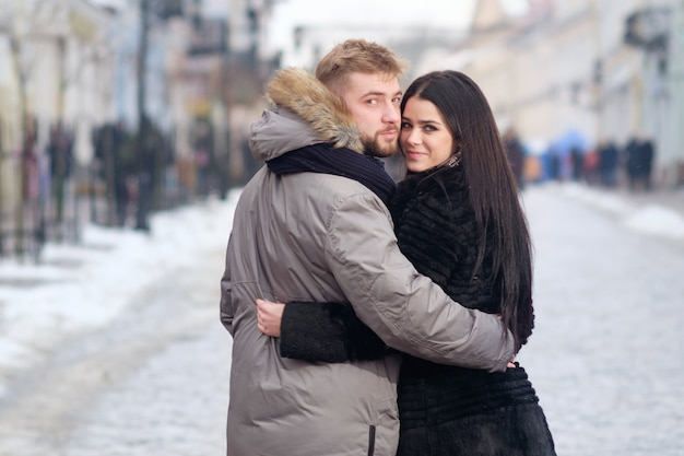 Young teen couple hug each other standing in center of street uner red umbrella in winter under snowfall, looking in eyes to each other and smiling
