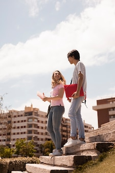 Young teen couple on stairs against cityscape