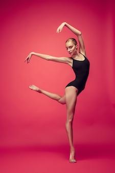 赤いスタジオの背景で踊る若い十代のダンサー。白人モデルのバレリーナプロジェクト。バレエ、ダンス、アート、コンテンポラリー、振り付けのコンセプト