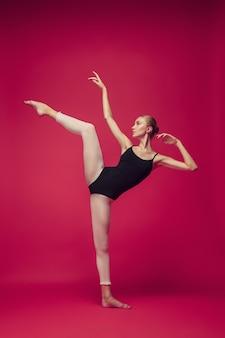Молодой подросток танцор танцует на красном фоне студии. проект балерины с кавказской моделью. концепция балета, танца, искусства, современности, хореографии