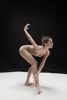 白い床のスタジオの背景で踊る若い十代のダンサー。バレリーナプロジェクト。
