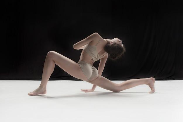Молодой подросток танцор танцует на белом полу студии