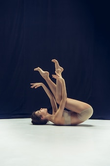 白い床のスタジオで踊る若いティーンダンサー