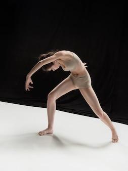Молодой подросток танцор танцует на белой студии пола.