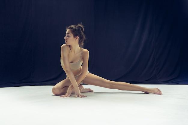 白い床のスタジオで踊る若いティーンダンサー。