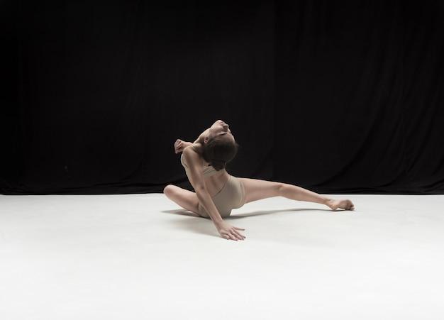 Young teen dancer dancing on white floor studio.