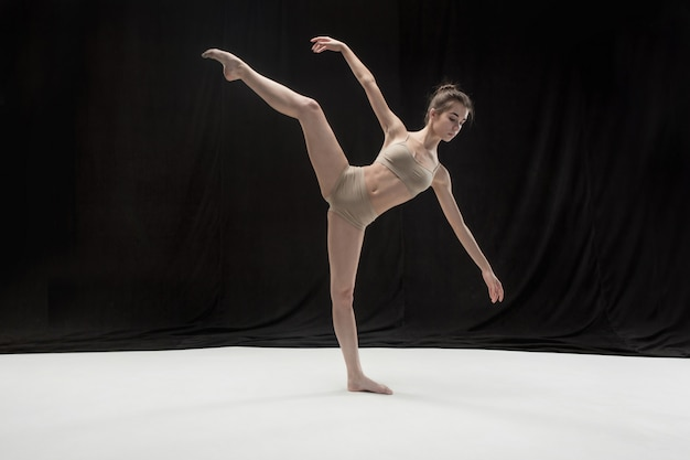 Young teen dancer on white floor space.