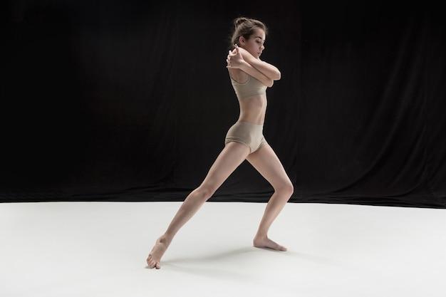 Giovane ballerino teenager sul pavimento bianco.