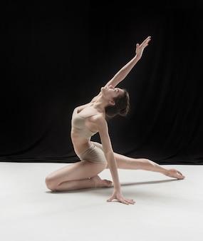 Giovane ballerina adolescente sul pavimento bianco