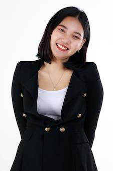 공식적인 검은 양복을 입은 젊은 10대 여성 사업가는 귀엽고 자신감 있는 미소를 지으며 현대 사무실에서 직장 생활을 시작합니다. 새로 졸업한 학생들과 취업 첫 날을 위한 개념.