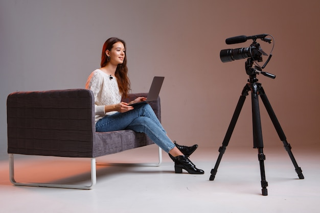 Young teen girl blogger makes a video stream on the couch at home