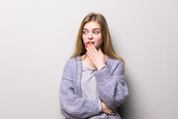 Young teen girl covers her mouth in shock hand on a gray wall