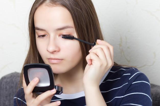 若い十代の少女は、パーティーや散歩に行く前にナチュラルメイクをし、眉毛、まつげをペイントします