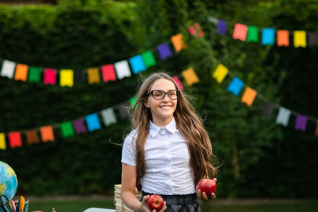 Young teen girl in glasses at white shirt holding red apples