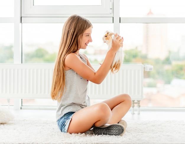 床にモルモットを保持している若い十代の少女