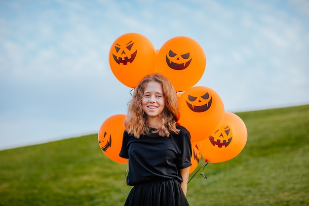 Молодая девушка-подросток в черной одежде держит кучу воздушных шаров хэллоуина на зеленом холме. скопируйте пространство. концепция праздника.