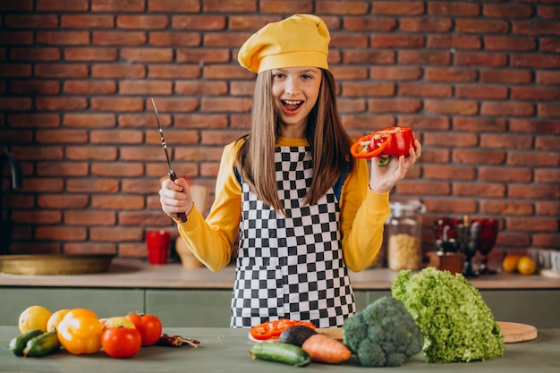 Young teen girl preparing salad for breakfast at the kitchen