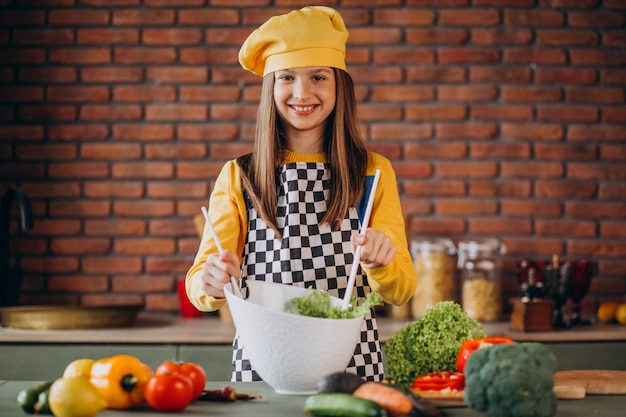 Giovane ragazza teenager che prepara insalata per la prima colazione alla cucina