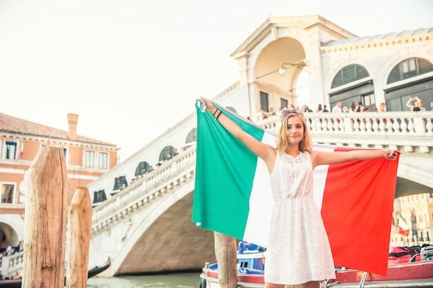 이탈리아 베니스(venice) 중심에 있는 역사적인 다리 폰테 데 리알토(ponte de rialto) 앞에 이탈리아 국기를 들고 있는 어린 10대 소녀 여행자.