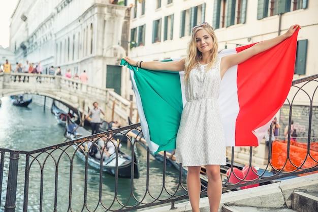 이탈리아 베니스의 중심에 있는 다리에 이탈리아 국기가 달린 어린 십대 소녀 여행자.