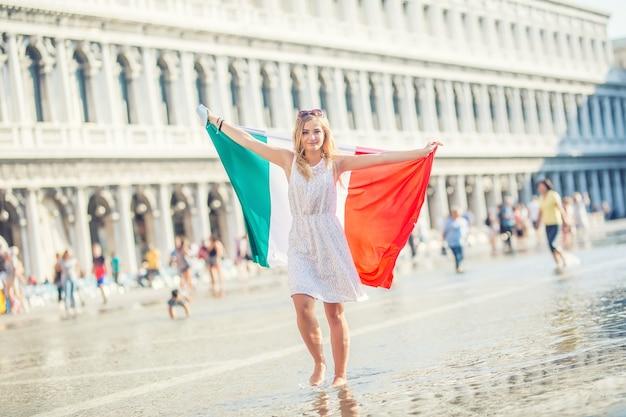 이탈리아 베니스의 산마르코 광장에 이탈리아 국기를 들고 있는 어린 십대 소녀 여행자.