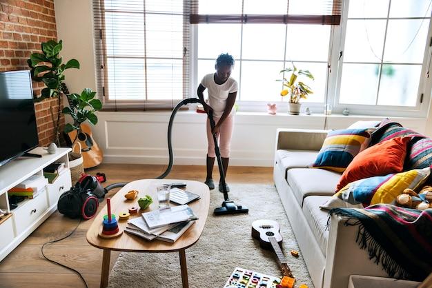 家の掃除機をかける若い十代の少女