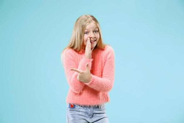 Giovane ragazza teenager che bisbiglia un segreto dietro la sua mano isolata sulla parete blu alla moda dello studio