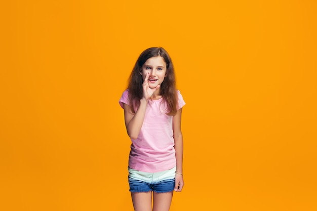 The young teen girl whispering a secret behind her hand over orange space