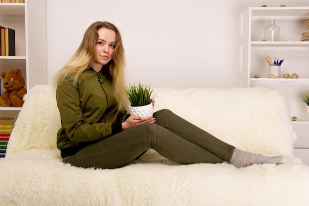 ソファに座って緑の観葉植物を保持しているにきび顔の若い十代の少女