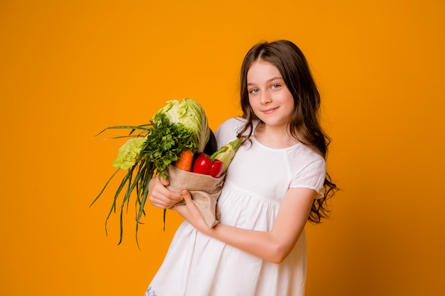 Young teen girl with a bag of vegetables