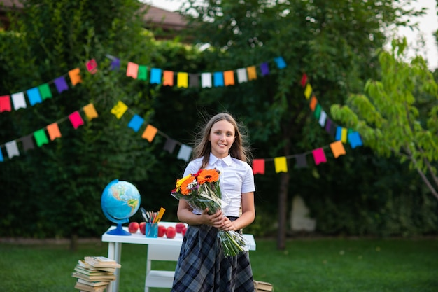 Молодая девушка с длинными волосами в школьной форме позирует с букетом цветов