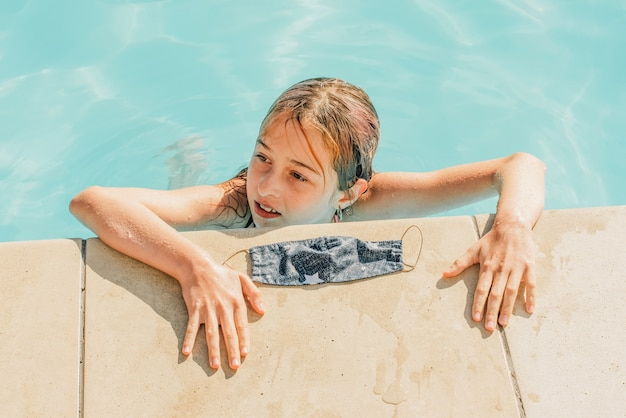 Молодая девушка с защитной маской внутри бассейна. концепция воздействия вспышки коронавируса на туристическую индустрию летом 2020 года. девушка плавает в бассейне в защитной маске
