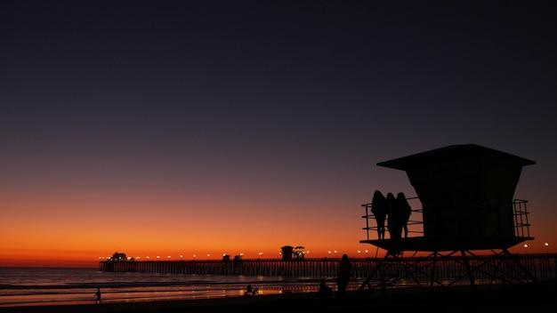 인명 구조원 타워 근처에 있는 어린 10대 소녀들의 실루엣, 태평양 해변의 친구들, 미국 캘리포니아주 오션사이드의 일몰 황혼. 알아볼 수 없는 십대, 사람, 그리고 황혼의 그라데이션 보라색 보라색 하늘.