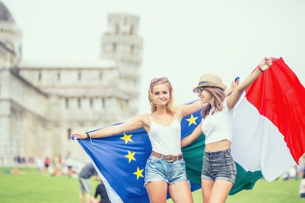 Young teen girls traveler with italian and european union flags  before the historic tower in town pisa - italy.