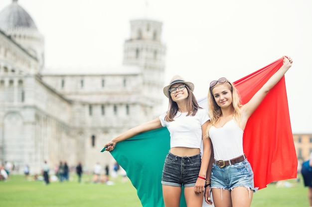 Young teen girls traveler with italian flag before the historic tower in town pisa - italy.