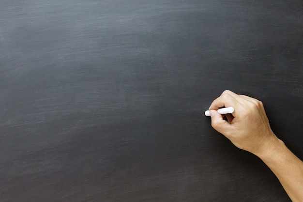 Young teen hand to draw and writing something on blackboard with chalk. education back to school concept, chalkboard.