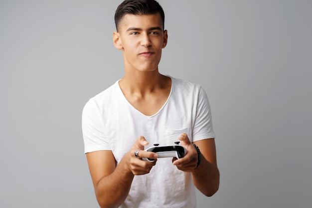 灰色の背景の上のコンソールジョイスティックで遊ぶ若い十代の男