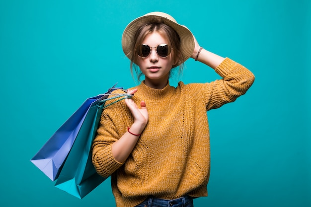 Young teen woman in sunglasses and hat holding shopping bags in her hands feeling so happiness isolated on green wall