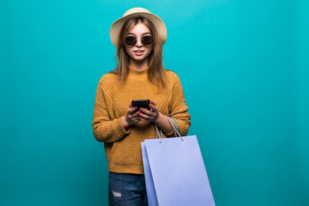 Young teen woman in sunglasses and hat looking something in smartphone and holding shopping bags in her hands feeling so happiness on green wall