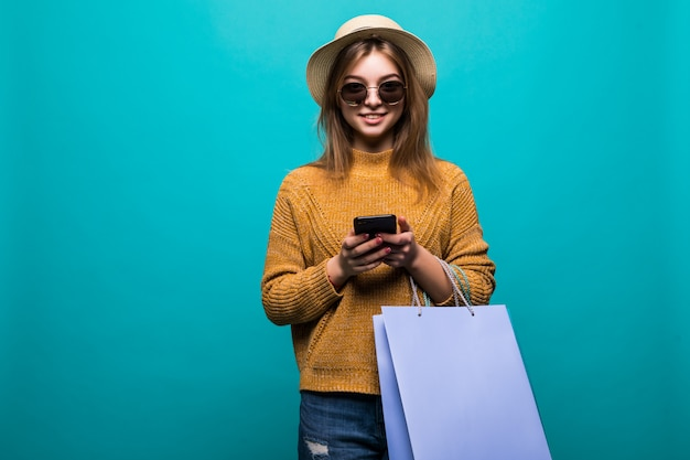 Young teen woman in sunglasses and hat looking something in smartphone and holding shopping bags in her hands