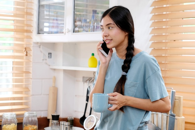 Young teenage asian woman talking phone in kitchen, asian girl holding coffee cup while talking smart phone with happiness in the morning, people and technology  lifestyle