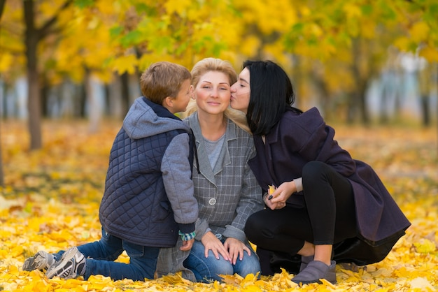 Young teenage boy and his elder sister kissing their mother in cheeks while sitting on the ground in park, on bright yellow leaves on bright autumn day