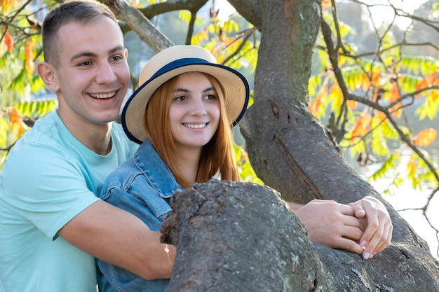 Young teenage couple outdoors. pretty girl with red hair and handsome boy hugging together.