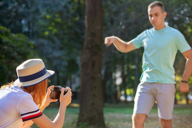 Young teenage couple taking pictures of one another outdoors in sunny summer park.