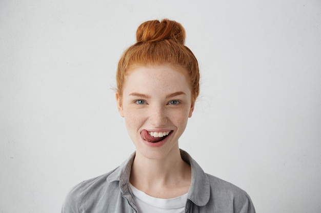 Young teenage female with ginger hair knot sticking out her tongue having funny look isolated.