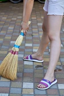 Молодая девочка-подросток, уборка булыжного пола на открытом воздухе
