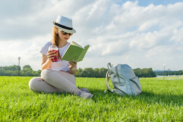 Young teenage girl in hat and glasses reads book