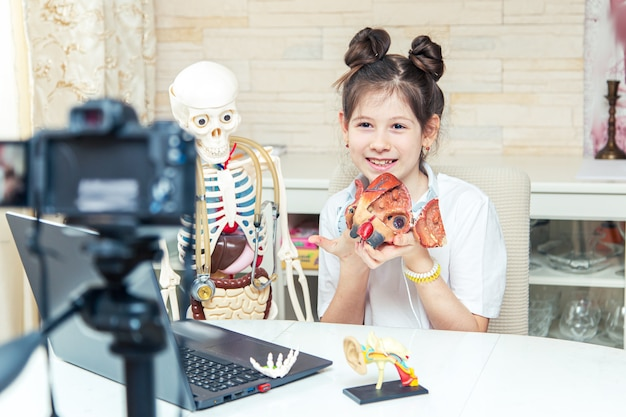 Young teenage girl is recording a video blog at home. she tells subscribers about human anatomy. unusual hobby.
