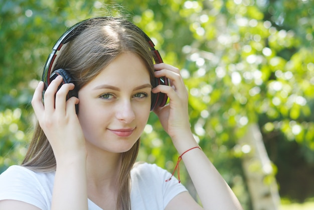 Young teenage girl listening music with headphones and smart phone in the park, summer portrait.
